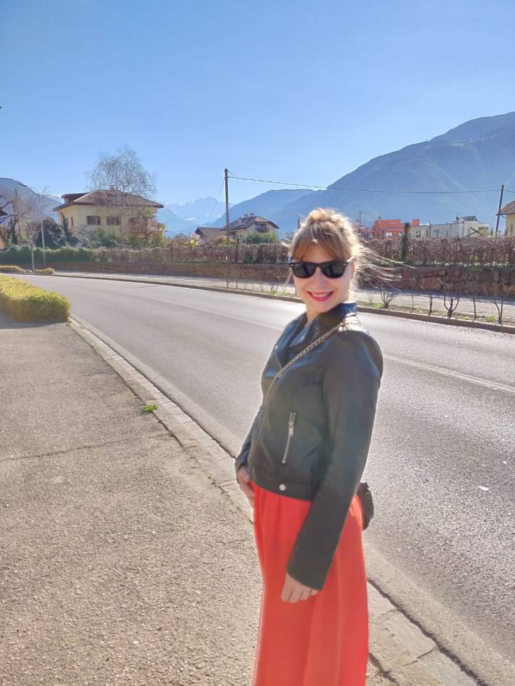 Martina, pregnant, smiling with a long orange skirt and a fake leather jacket.